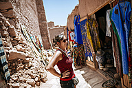 Morocco, Ouarzazate, tourist standing in front of clothing shop - KIJF01005