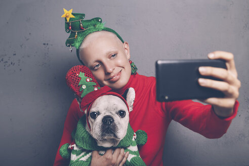 Woman with French bulldog taking selfie with smartphone at Christmas time - RTBF00532