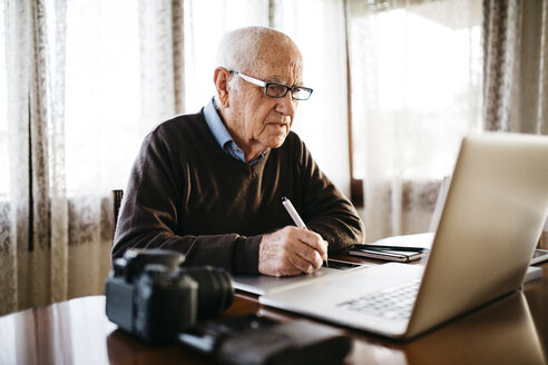 Senior photographer working with laptop at home - JRFF01051