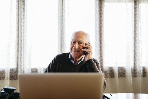 Portrait of smiling senior man on the phone at home - JRFF01060