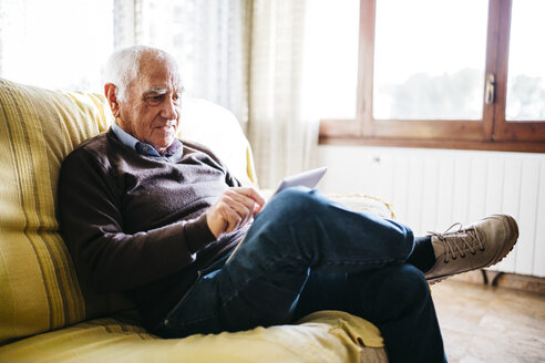 Senior man sitting on couch using tablet - JRFF01066
