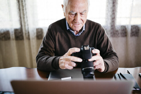 Senior photographer with laptop and digital camera at home - JRFF01069