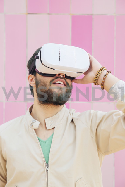 Man wearing Virtual Reality Glasses in front of the pink wall - RTBF00534