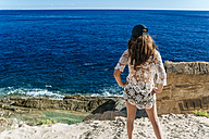 Spain, Ibiza, Woman standing on beach, looking at the sea - KIJF01019