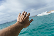 Hand reaching out for distant motor boat - KIJF01025