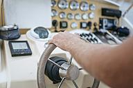 Man steering motor boat, close up - KIJF01028