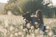 Young woman and her dog in field of flowers at twilight - SKCF00224