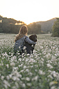 Young woman and her dog sitting in field of flowers at twilight - SKCF00230
