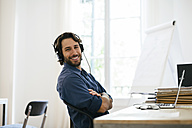 Businessman in office using headphones at desk - EBSF01943