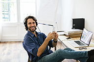 Businessman in office using headphones and smart phone, feet up - EBSF01946