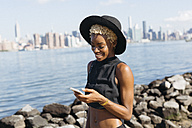 USA, New York City, Brooklyn, smiling young woman at East River looking on cell phone - GIOF01647