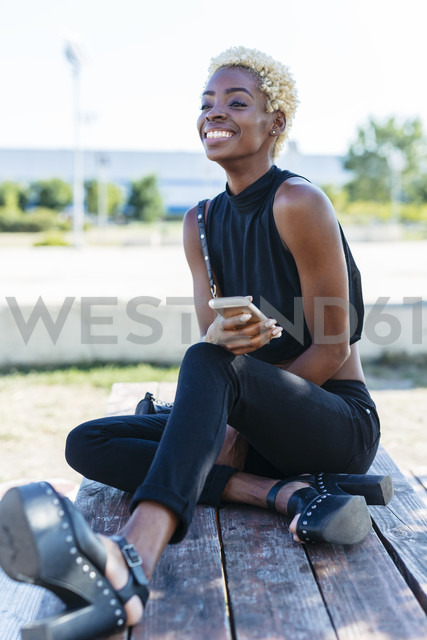Smiling young woman sitting on bench holding cell phone - GIOF01659