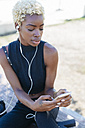 Young woman with cell phone and earbuds - GIOF01662