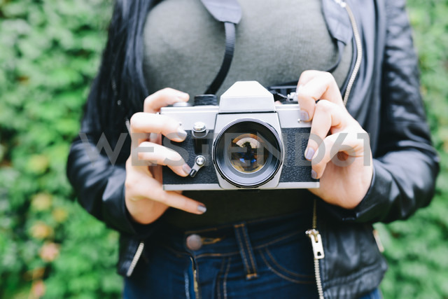 Woman's hands holding analogue camera, close-up - GEMF01287