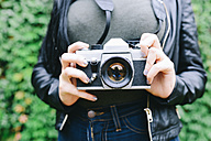 Woman's hands holding analogue camera, close-up - GEMF01287