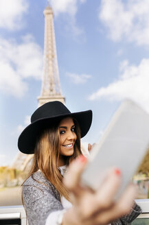 France, Paris, smiling woman taking a selfie in front of Eiffel Tower - MGOF02633