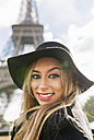 France, Paris, portrait of smiling woman in front of Eiffel Tower - MGOF02639