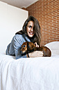Smiling young woman lying in bed with her dog - VABF00859