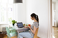 Woman at home sitting at table using laptop - FKF02084