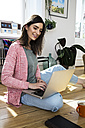 Woman at home sitting on floor using laptop - FKF02093