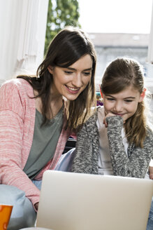 Smiling mother and daughter using laptop - FKF02096