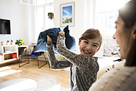 Happy mother with daughter at home having a pillow fight - FKF02105