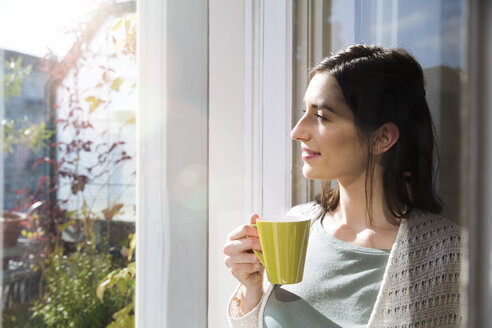 Smiling woman holding cup of coffee at the window - FKF02114