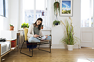Woman at home sitting on chair reading book - FKF02120