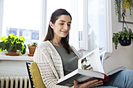 Smiling woman at home sitting on chair reading book - FKF02123