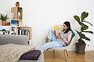 Woman at home sitting on chair reading book - FKF02126