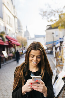 France, Paris, young woman looking at cell phone in Montmartre - MGOF02649