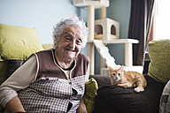 Portrait of happy woman and her cat sitting on couch in the living room - RAEF01591