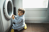 Baby boy crouching in front of washing machine - JASF01362
