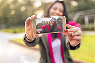 Young woman taking a selfie in a park in autumn - MGOF02653