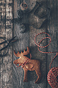 Elk-shaped cookie, cookie cutter, scissors and string on dark wood - RTBF00537