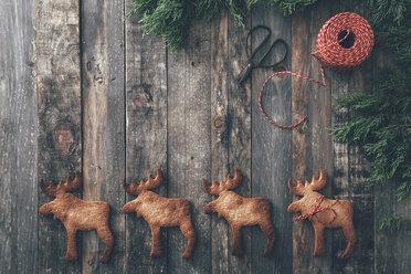 Row of four Elk-shaped Christmas cookies on dark wood - RTBF00549