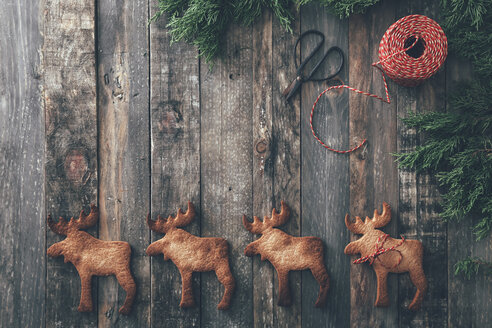 Row of four Elk-shaped Christmas cookies on dark wood - RTBF00549