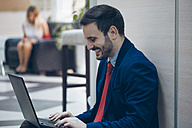 Laughing businessmann using laptop in office - ZEDF00447