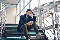 Pensive businessmann sitting on stairs looking at cell phone - ZEDF00450