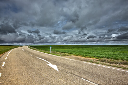 Spain, Province of Zamora, empty road under cloudy sky - DSGF01200