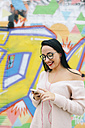 Portrait of happy young woman with earphones and cell phone in front of graffiti wall - GEMF01290