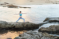 Pregnant woman practising yoga at the sea - DIGF01453