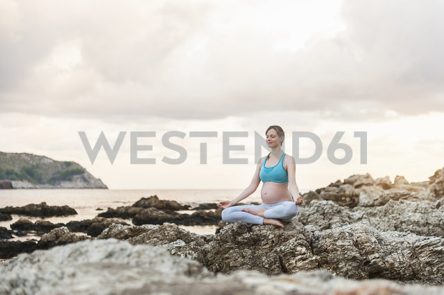 Pregnant woman practising yoga at the sea - DIGF01465 - Daniel Ingold/Westend61