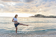 Happy pregnant woman on the beach splashing with water - DIGF01477