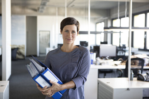 Businesswoman in office holding folders - RBF05231