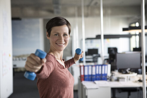Smiling businesswoman in office exercising with dumbbells - RBF05246