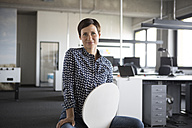 Portrait of smiling businesswoman in office sitting on chair - RBF05252