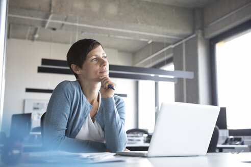 Businesswoman in office with laptop thinking - RBF05261