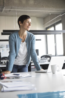 Smiling businesswoman leaning on office desk - RBF05267