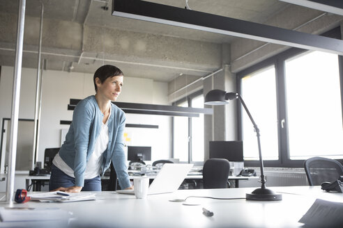 Businesswoman in office with laptop thinking - RBF05270